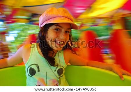 Little girl having fun in a carousel  - stock photo