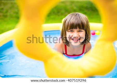Little girl having fun in the garden swimming pool. - stock photo