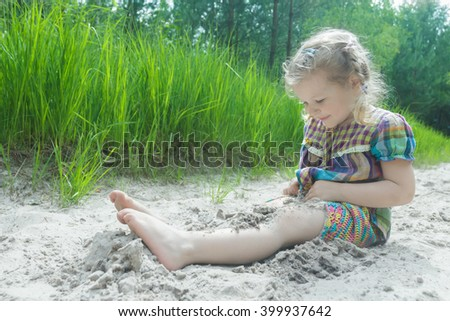Little girl having fun on beach dune and burying herself in white sand at summer pinewood background