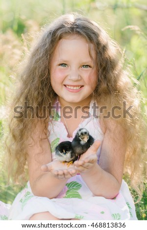 Little girl having fun playing with duck or chicken. Toddler kids outdoor. Happy child laughing and smiling.