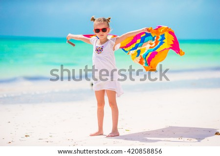 Little girl having fun running with towels on tropical beach