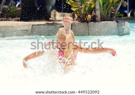 Little girl having fun time in the swim pool - stock photo