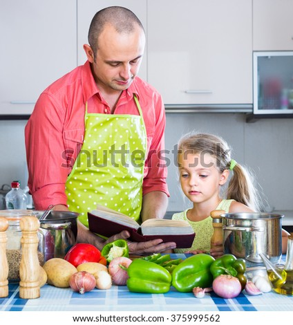 Little girl helping adult father to prepare dinner indoors - stock photo