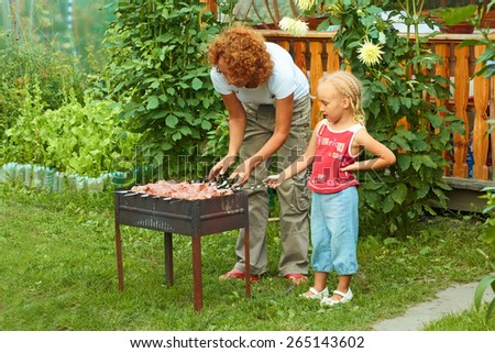 Little girl helping her mother to cook shish kebab for a picnic outdoors - stock photo