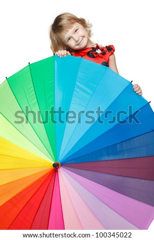 Little girl hiding behind a colorful umbrella - stock photo
