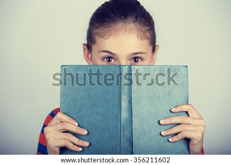 Little girl hiding herself behind book, studying, loving to learn.Cute little girl  hiding behind a book, isolated over white. - stock photo