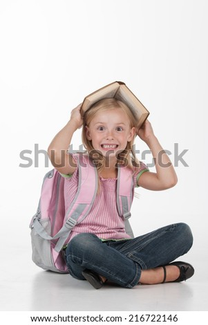 Little girl hiding under big book. cute girl sitting on floor on white background - stock photo