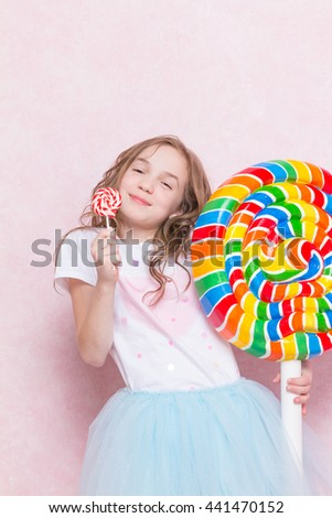 Little girl hold big lollipop against pink wall - stock photo