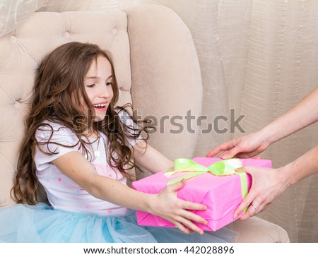 little girl hold girt box. She receiving box from mother's hands - stock photo