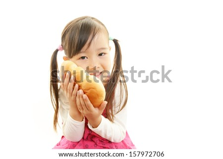 Little girl holding a bread - stock photo