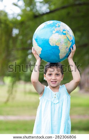 Little girl holding a globe on a sunny day - stock photo
