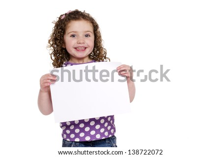 Little girl holding a plain white sign isolated on a white background smiling at the camera - stock photo