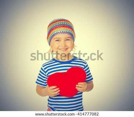 Little girl holding a red heart toy. Isolated on a gray background. - stock photo