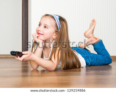 little girl holding a remote control - stock photo