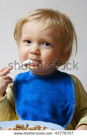 little girl holding a spoon at her arms and eating a pap