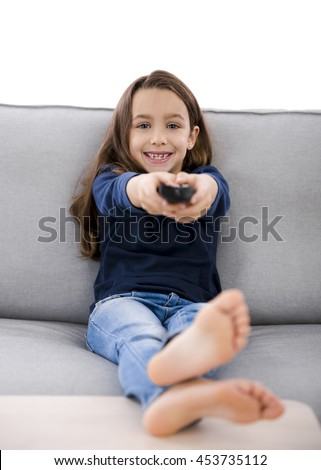 Little girl holding a TV remote control - stock photo