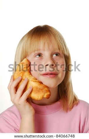 Little girl holding and eating croissant. Little kid eating bread. - stock photo