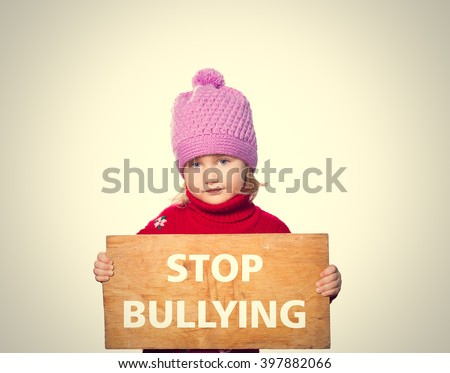 Little girl holding Board with text STOP BULLYING. Isolated on gray background. - stock photo