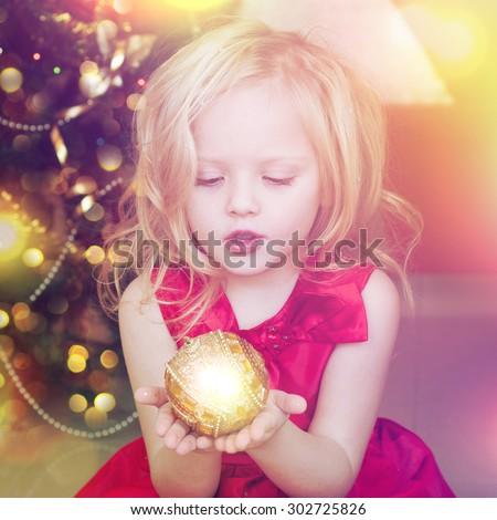Little girl  holding christmas ornament - stock photo