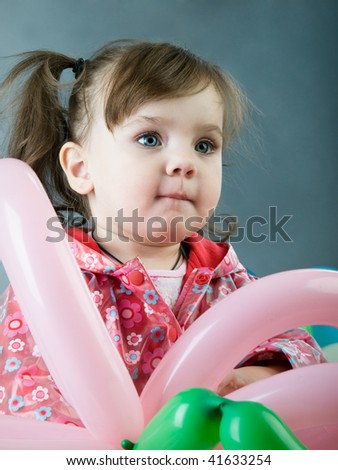 little girl holding colorful balloons on a grey background