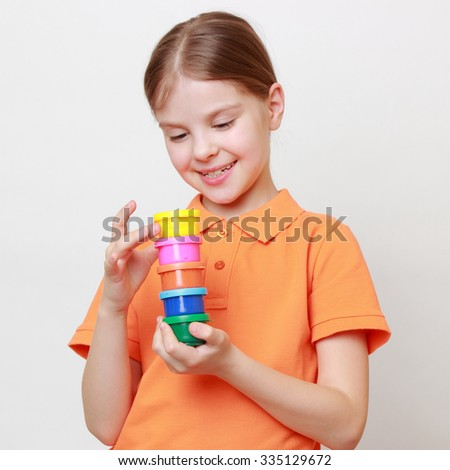 little girl holding colorful paints - stock photo