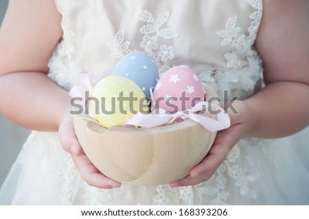 Little girl  holding easter eggs - stock photo