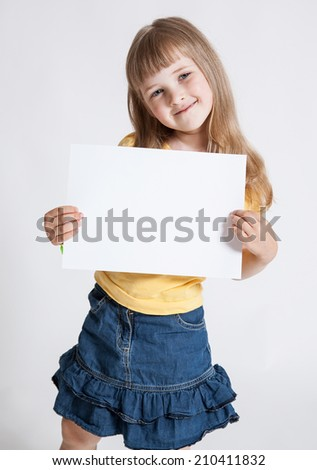 Little girl holding empty sheet of a paper, white backgroung - stock photo