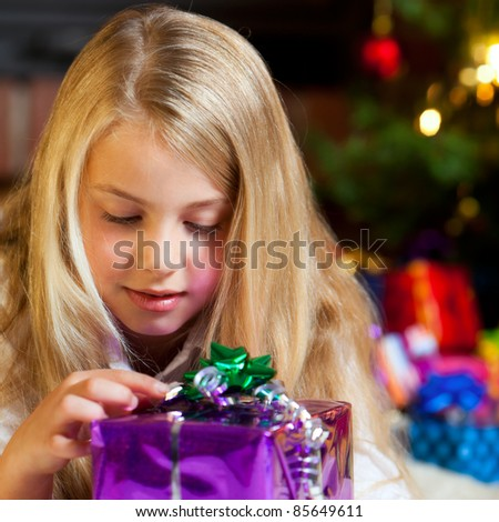little girl holding gift christmas tree and gifts in background - stock photo