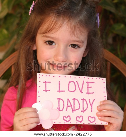 little girl holding hand-made valentine card with I love Daddy