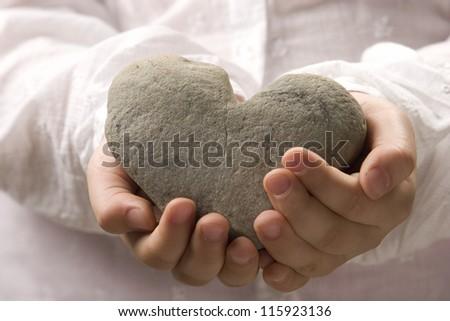 Little Girl Holding Heart-Shaped Rock - stock photo