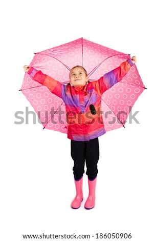 Little girl holding her big pink umbrella like wings - stock photo