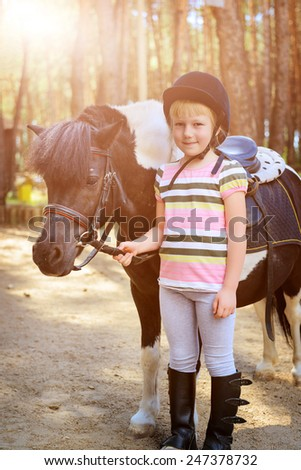 Little girl holding her pony. Filtered image - stock photo