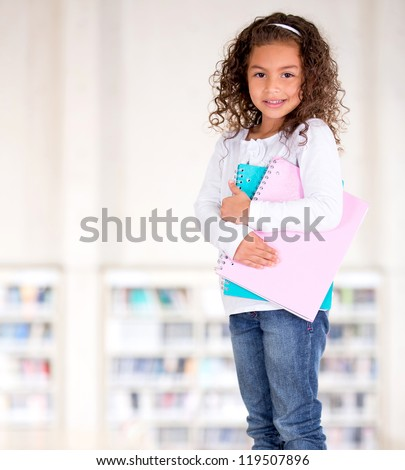 Little girl holding notebooks at the school library - stock photo