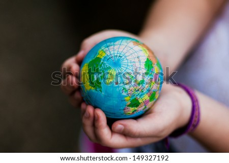 Little girl holding the earth in her hands. Earth day. Green concept - stock photo
