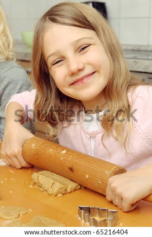 Little girl holding the rolling-pin ans smiling in the camera - stock photo