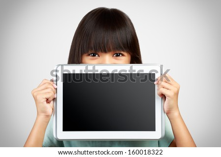 Little girl holding up a blank tablet computer obscuring the lower half of her face with the screen - stock photo