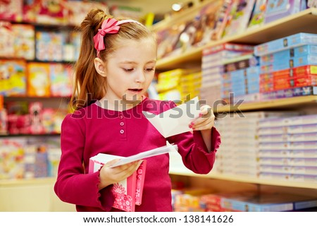 Little girl holds pack of envelopes in one hand and one open envelope in another - stock photo