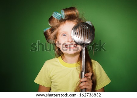 Little girl housewife  look through kitchenware - stock photo