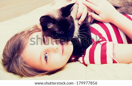 little girl hugging a cat  - stock photo