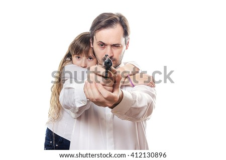 Little girl hugging her father who is aiming a gun