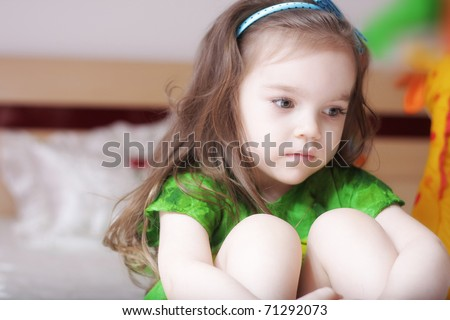 little girl hugging her knees so sad - stock photo