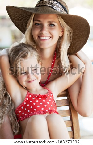 Little girl hugging her mother in a tropical cafe. Outdoors. - stock photo