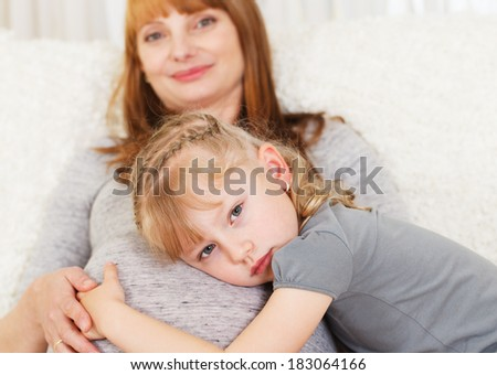 Little girl hugging her mothers belly. - stock photo