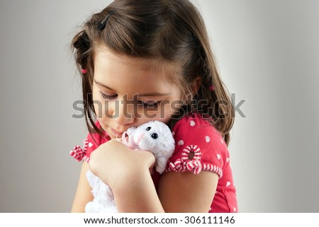 Little girl hugging plush lamb or stuffed toy over grey - stock photo