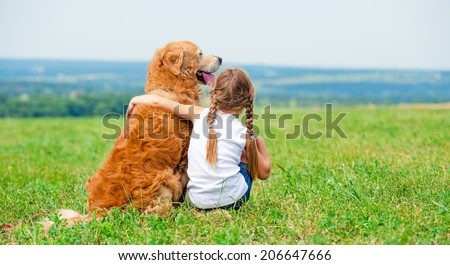 Little girl hugging retriever in the field, looking into the distance - stock photo