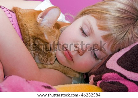 little girl hugging tabby cat in bed - stock photo