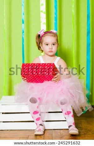Little girl in a beautiful dress with gift box