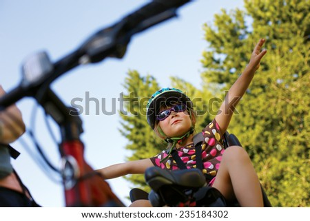 Little girl in a bicycle seat - stock photo
