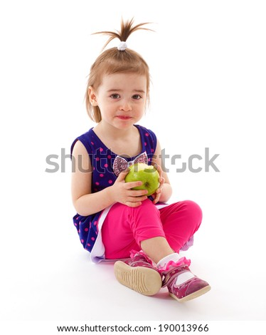 Little girl in a blue dress eating an apple on a white background