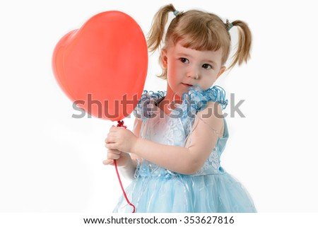 Little girl in a blue dress holding a red balloon in the shape of a heart on a white background